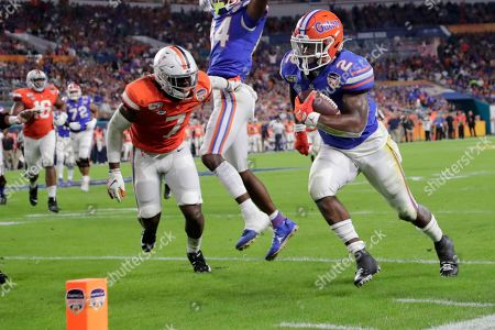 Florida running back Lamical Perine (2) runs past Virginia safety Chris Moore (7) to score a touchdown during the first half of the Orange Bowl NCAA college football game, in Miami Gardens, Fla