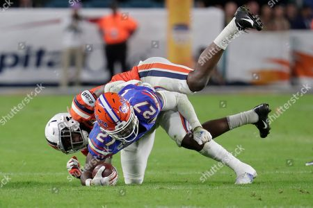 Virginia running back Dameon Pierce (27) gets a first down as he is tackled by Virginia safety Chris Moore during the first half of the Orange Bowl NCAA college football game, in Miami Gardens, Fla