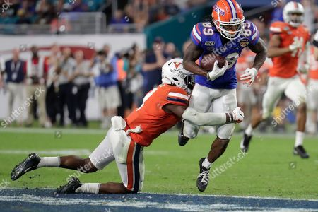 Florida wide receiver Tyrie Cleveland (89) runs for a first down as Virginia safety Chris Moore defends during the second half of the Orange Bowl NCAA college football game, in Miami Gardens, Fla