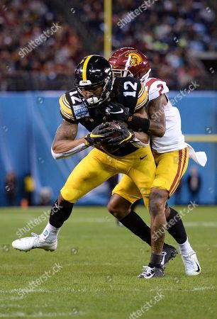 Iowa wide receiver Brandon Smith (12) is tackled by Southern California cornerback Olaijah Griffin during the first half of the Holiday Bowl NCAA college football game, in San Diego