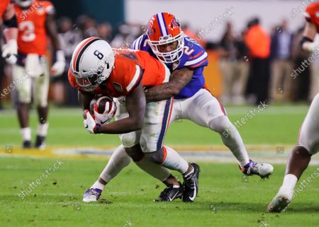 Virginia Cavaliers wide receiver Hasise Dubois (8) runs with the ball in the fourth quarter tackled by Florida Gators defensive back Brad Stewart Jr. (2) during the Capital One Orange Bowl - NCAA Football game at the Hard Rock Stadium in Miami Gardens, Florida. Florida defeated Virginia 36-28