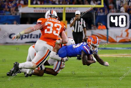 Florida Gators wide receiver Tyrie Cleveland (89) secures a pass tackled by Virginia Cavaliers linebacker Noah Taylor (14), as linebacker Zane Zandier (33) follows the action, during the Capital One Orange Bowl - NCAA Football game at the Hard Rock Stadium in Miami Gardens, Florida. Florida defeated Virginia 36-28