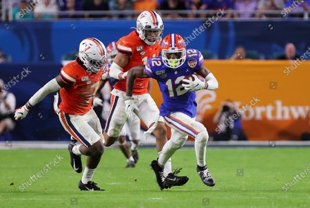 Florida Gators wide receiver Van Jefferson (12) runs with the ball, pressured by Virginia Cavaliers cornerback Nick Grant (1), left, and linebacker Noah Taylor (14), center, during the Capital One Orange Bowl - NCAA Football game at the Hard Rock Stadium in Miami Gardens, Florida. Florida defeated Virginia 36-28