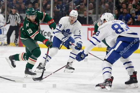 Minnesota Wild center Luke Kunin skates with the puck with pressure from Toronto Maple Leafs defenseman Cody Ceci (83) and Maple Leafs center Auston Matthews (34) in the first period of an NHL hockey game, in St. Paul, Minn