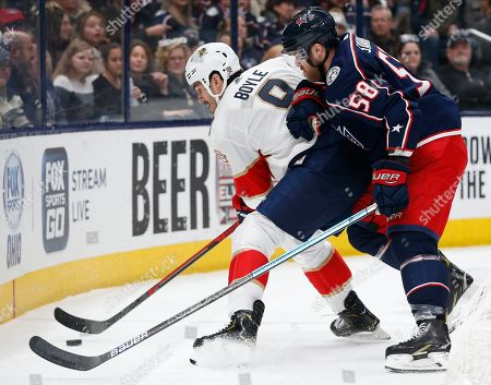 Florida Panthers' Brian Boyle, left, tries to control the puck as Columbus Blue Jackets' David Savard defends during the first period of an NHL hockey game, in Columbus, Ohio