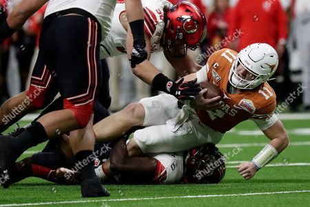 Sam Ehlinger, Scott Foley, Devin Lloyd. Texas quarterback Sam Ehlinger (11) is stopped on a run by Utah defensive tackle Viane Moala (98) and linebacker Devin Lloyd, bottom, during the first half of the Alamo Bowl NCAA college football game in San Antonio
