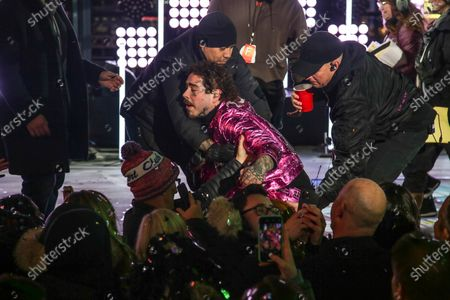 Stock Picture of American singer Post Malone (C) is helped by staff after falling during New Year's Eve celebrations at Time Square, New York, USA, 01 January 2020.
