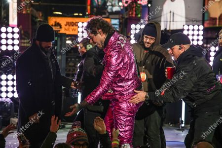 American singer Post Malone (C) is helped by staff after falling during New Year's Eve celebrations at Time Square, New York, USA, 01 January 2020.