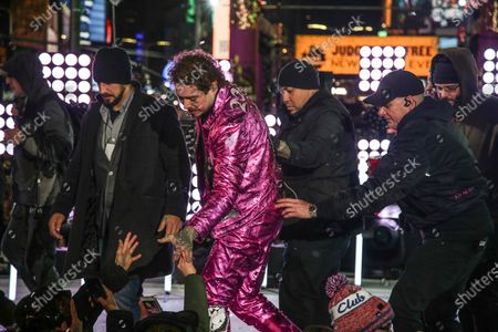 Stock Photo of American singer Post Malone (C) is helped by staff after falling during New Year's Eve celebrations at Time Square, New York, USA, 01 January 2020.