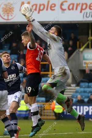Bartosz Bialkowski of Millwall saves ahead of James Collins of Luton Town during Millwall vs Luton Town, Sky Bet EFL Championship Football at The Den on 1st January 2020