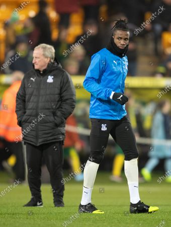 Stock Image of Wilfried Zaha of Crystal Palace warms-up before the match and runs past Assistant Ray Lewington