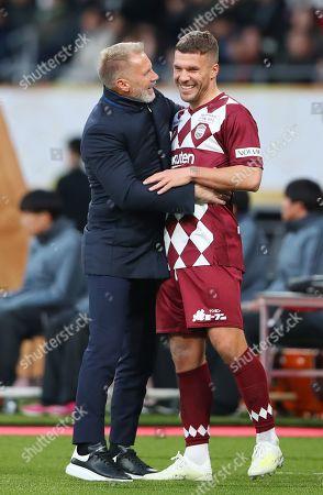 Thorsten Fink and Lukas Podolski of Vissel Kobe during the match