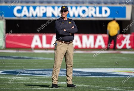 Orlando, FL, U.S: Michigan Wolverines head coach Jim Harbaugh watches the special teams warm up before the start of VRBO Citrus Bowl game between Alabama Crimson Tide and the Michigan Wolverines at Camping World Stadium in Orlando, Fl