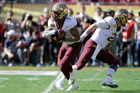 Minnesota running back Rodney Smith (1) takes a handoff from quarterback Tanner Morgan during the first half of the Outback Bowl NCAA college football game, in Tampa, Fla