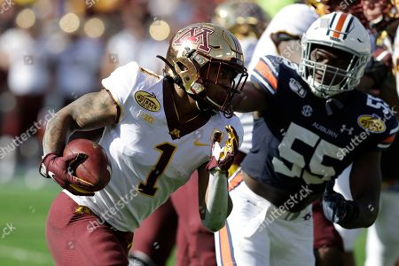 Minnesota running back Rodney Smith (1) slips a takcle by Auburn defensive end T.D. Moultry (55) during the first half of the Outback Bowl NCAA college football game, in Tampa, Fla