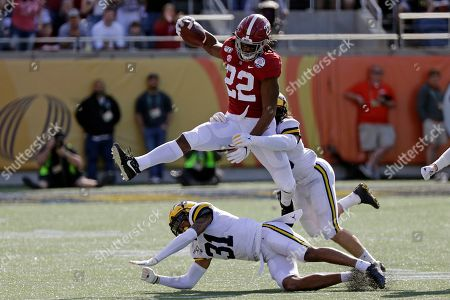 Alabama running back Najee Harris (22) gains yardage as he tries to get past Michigan defensive back Vincent Gray (31) and defensive back DeMarcco Hellams, right, during the first half of the Citrus Bowl NCAA college football game, in Orlando, Fla