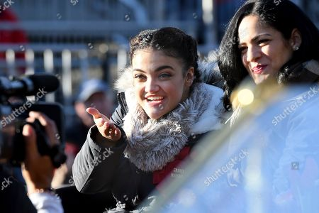 Grand Marshal Laurie Hernandez, left, motions to a television camera at the 131st Rose Parade in Pasadena, Calif