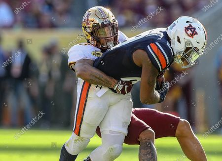 Minnesota's Chris Williamson #6 tackles Auburn's JaTarviousWhitlow #28 during the Outback Bowl football game between the Minnesota Golden Gophers and the Auburn Tigers at Raymond James Stadium in Tampa, FL
