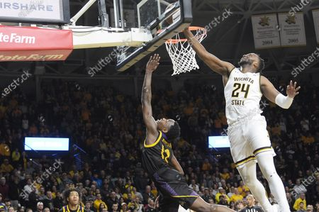 East Carolina Pirates guard Tremont Robinson-White (12) lays the ball up to score as Wichita State Shockers center Morris Udeze (24) goes up to block the shot during the NCAA Basketball Game between the East Carolina Pirates and the Wichita State Shockers at Charles Koch Arena in Wichita,Kansas