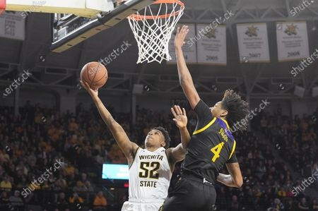 Wichita State Shockers guard Grant Sherfield (52) lays the ball in for two points as East Carolina Pirates forward Brandon Suggs (4) attempts the block during the NCAA Basketball Game between the East Carolina Pirates and the Wichita State Shockers at Charles Koch Arena in Wichita,Kansas