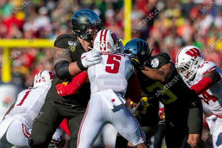 Pasadena, CA, USA : Oregon Ducks offensive lineman Calvin Throckmorton (54) and wide receiver Johnny Johnson III (3) blocks Wisconsin Badgers cornerback Rachad Wildgoose (5) from breaking into the backfield during the 106th Rose Bowl game. ©Maria Lysaker/CSM