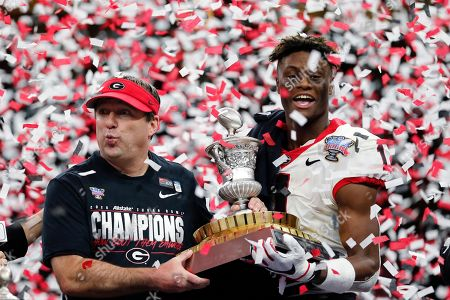 Georgia head coach Kirby Smart and wide receiver George Pickens (1), MPV for the game, hoist the trophy after the Sugar Bowl NCAA college football game against Baylor in New Orleans, . Georgia won 26-14
