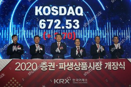 """Jung Ji-won, third from right, chief executive of the Korea Exchange, and Financial Services Commission Chairman Eun Sung-soo, third from left, applaud with other participants during the opening of this year's trading in Seoul, South Korea, . The sign read: """"Opening ceremony of 2020 trading"""