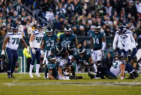 Travis Homer, Running Back of the Seattle Seahawks (25), is tackled by Rodney McLeod, Safety of the Philadelphia Eagles (23), and Anthony Rush, Defensive Tackle of the Philadelphia Eagles (66)