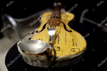 Stock Photo of View of a violin made from recycled materials, such as a fork and a spoon, belonging to a young musician of the Orchestra of Recycled Instruments of Cateura during a press preview of their concert in Madrid, Spain, 02 January 2020. The orchestra, made up of children and youth at risk of exclusion from a slum in Asuncion, Paraguay, is to play their New Year's charity concert with Spanish singer Luz Casal, Flamenco dancer Sara Baras and the Madrid Gospel Choir at Madrid's Royal Palace later the same day. Their instruments are made from forks, spoons, old radiographies, pipes and other recycled materials recovered from the landfill site of Cateura, Paraguay.