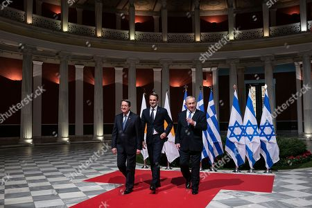 Greece's Prime Minister Kyriakos Mitsotakis, center, Cypriot President Nicos Anastasiadis, left, and Israeli Prime Minister Benjamin Netanyahu walk towards a hall for a signing ceremony in Athens, . The leaders of Greece, Israel and Cyprus met in Athens Thursday to sign a deal aiming to build a key undersea pipeline, named EastMed, designed to carry gas from new rich offshore deposits in the southeastern Mediterranean to continental Europe
