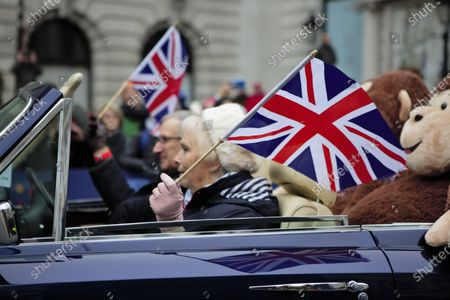 Members of Rolls Royce club holding UK Flags drive through the parade.