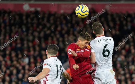 Liverpool's Roberto Firmino, center, jumps for the ball with Sheffield United's John Egan, left, and Sheffield United's Chris Basham during the English Premier League soccer match between Liverpool and Sheffield United at Anfield Stadium, Liverpool, England