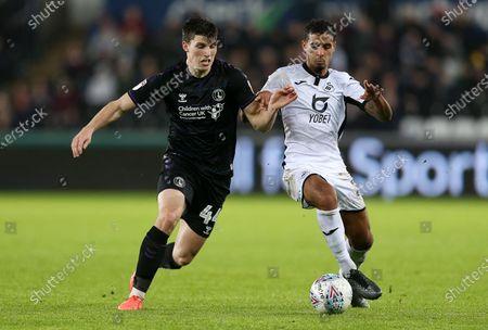 Josh Davison of Charlton Athletic is challenged by Kyle Naughton of Swansea City.