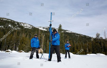 Stock Photo of Ramesh Gautam, Sean de Guzman, Lauren Miller. Sean de Guzman, center, chief of snow surveys for the California Department of Water Resources, plunges a snow survey tube into the snowpack during the first snow survey of the season at Phillips Station near Echo Summit, Calif., . The survey found the snowpack at 33.5 inches deep with a water content of 11 inches which is 97% of average at this location at this time of year. Also seen are DWR's Ramesh Gautam, left, and Lauren Miller