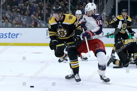 Joakim Nordstrom, Alexander Wennberg. Boston Bruins center Joakim Nordstrom (20) and Columbus Blue Jackets center Alexander Wennberg (10) compete for the puck in the second period of an NHL hockey game, in Boston
