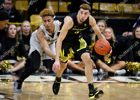 R m. Oregon guard Chris Duarte, front, picks up a loose ball as Colorado guard D'Shawn Schwartz defends in the second half of an NCAA college basketball game, in Boulder, Colo. Colorado won 74-65