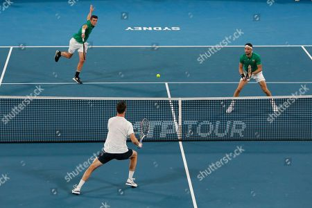 Grigor Dimitrov and Alexander Lazarov of Bulgaria, top, return the ball to British pair Jamie Murray and Joe Salisbury, centre, during their ATP Cup tennis match in Sydney, Australia