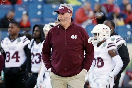 Mississippi State head coach Joe Moorhead watches as players warm up before the Music City Bowl NCAA college football game against Louisville, in Nashville, Tenn. Two people with knowledge of the situation say Mississippi State has fired coach Joe Moorhead after just two seasons. They spoke to The Associated Press on condition of anonymity because an announcement had not yet been made by the school. A meeting was scheduled, with Moorhead and athletic director John Cohen