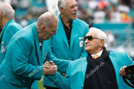 Former Miami Dolphins head coach Don Shula, right, is greeted on the field by former players from the Dolphins 1972 undefeated team during half time at an NFL football game against the Cincinnati Bengals, in Miami Gardens, Fla. Shula will turn 90 on