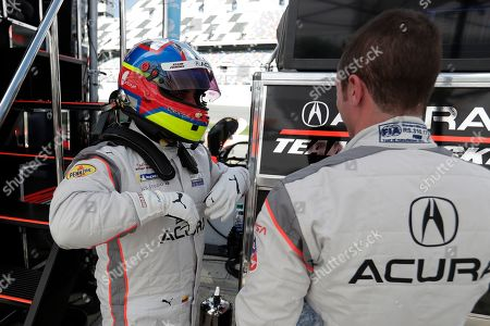Dane Cameron, right, prepares to go out on the track after Juan Pablo Montoya, left, comes in for a break during testing for the upcoming Rolex 24 hour auto race at Daytona International Speedway, in Daytona Beach, Fla