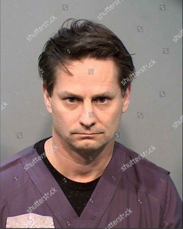 This undated booking photo provided by the Arizona Attorney General's Office shows Dr. Michael Lee Ham. The ophthalmologist and eye surgeon who runs clinics in metro Phoenix and the Prescott area has been arrested after he was indicted for running what is described as a years-long billing scheme, state Attorney General Mark Brnovich announced . The indictment accuses Ham, 52, of defrauding Medicare, the Veterans Affairs Department, Arizona's Medicaid agency and private insurers by fraudulent billing for laser or cataract surgeries at eight Kokopelli Eye Institute clinics