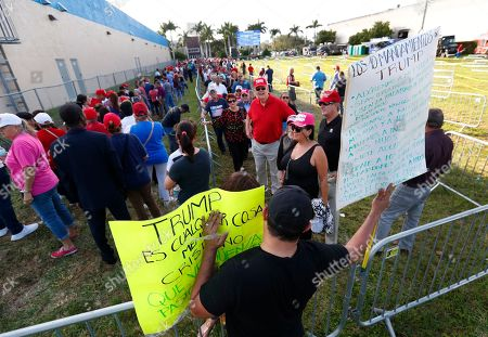 Andrew Gillum. Demonstrator Francisco Morales, foreground, holds signs outside the King Jesus International Ministry, as Trump supporters stood in line for a rally with President Donald Trump, in Miami
