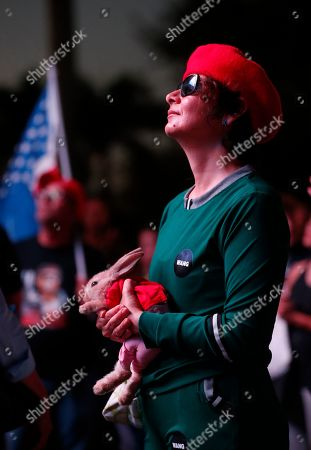 Andrew Gillum. A Trump supporter holding a rabbit watches President Donald Trump on a large screen in an overflow area outside the King Jesus International Ministry, during a rally with Trump, in Miami