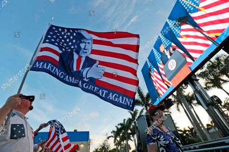 Stock Image of David Brantley, Andrew Gillum. David Brantley, left, holds an American flag with an image of President Donald Trump, as he watches the president on a large screen in an overflow area outside the King Jesus International Ministry, during a rally with Trump, in Miami