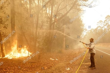 A man uses a water hose to battle a fire near Moruya, Australia, . Australia's Prime Minister Scott Morrison called up about 3,000 reservists as the threat of wildfires escalated Saturday in at least three states with two more deaths, and strong winds and high temperatures were forecast to bring flames to populated areas including the suburbs of Sydney