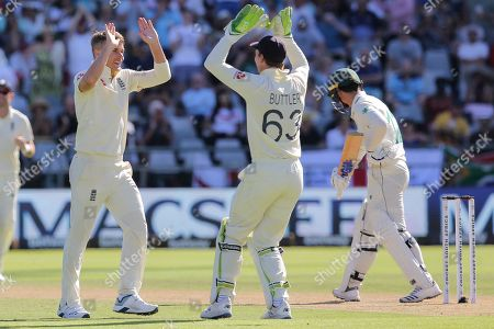 England bowler Dom Bess and England wicketkeeper Jos Buttler celebrate the wicket of Quinton De Kock during day two of the second cricket test between South Africa and England at the Newlands Cricket Stadium in Cape Town, South Africa