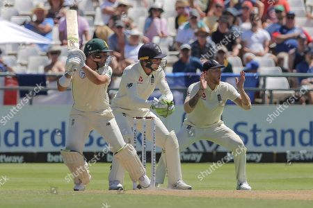 South African batsman Dean Elgar plays a shot while England wicketkeeper Jos Buttler and Ben Stokes watch on during day two of the second cricket test between South Africa and England at the Newlands Cricket Stadium in Cape Town, South Africa