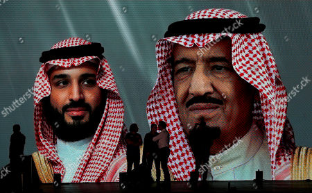Dakar Rally organizers stand in front of a screen displaying images of Saudi King Salman, right, and Crown Prince Mohammed bin Salman, during a presentation in Dakar village, in Jiddah, Saudi Arabia, . The Dakar Rally is swapping South America for Saudi Arabia. Created in 1977, the rally was raced across Africa until terror threats in Mauritania led organizers to cancel the 2008 edition