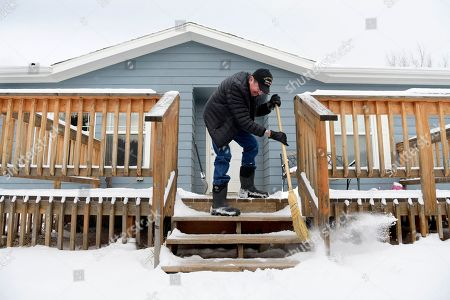 Richard King, 70, sweeps off the front steps to his home near Zortman, Mont., on the Fort Belknap Indian Reservation on . King retired on disability in 2016 after serving as the director of the Fort Belknap Chemical Dependency Center