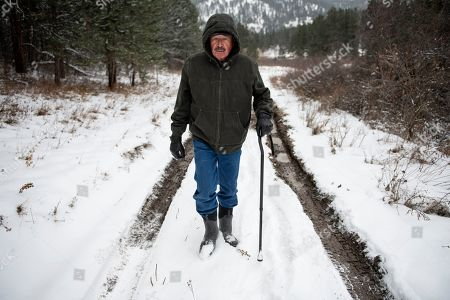 """Richard King, 70, walks down a muddy road on the family ranch near Zortman, Mont., on . """"It's called complete serenity."""" King said of living on the ranch. """"Its close as you can get to God living here"""